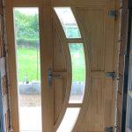 Lucc fenyőből készült fa bejárati ajtó, fix oldalvilágítóval.