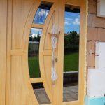 Lucc fenyőből készült fa bejárati ajtó, fix oldalvilágítóval, szürke reflexiós katedráll üveggel.