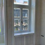 Tok osztott 92mm-es keresztmetszetű fa ablak felül bukó, alul kétszárnyú középen felnyíló bukó-nyíló, mélybéléssel, radiátor takarással, beépítve.